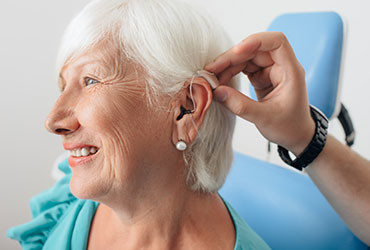 An elderly woman smiles while being fitted with an advanced hearing aid